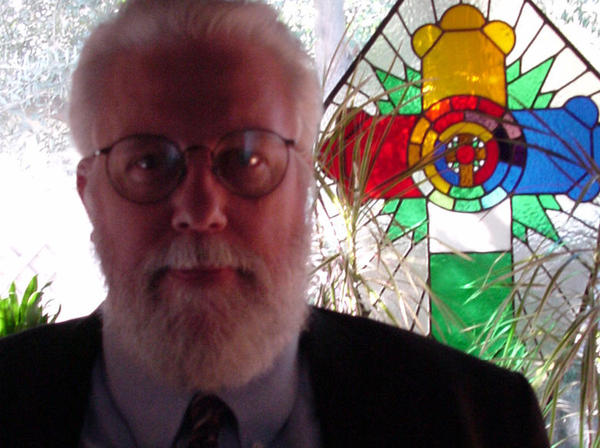 Lon Duquette in front of a stained glass window.